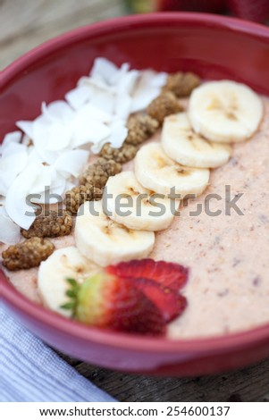 Trendy porridge decorated with fruits and coconut chips - stock photo
