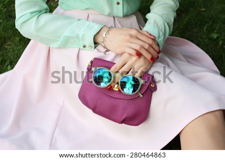 Trendy romantic style woman with purple little bag in her hands . Outdoor shot - stock photo