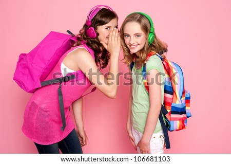 Trendy schoolgirls sharing a secret with each other. All on pink background - stock photo