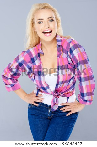 Trendy sexy blond woman standing with her hands on her hips laughing at the camera  three quarter pose on grey - stock photo