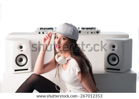 Trendy sexy young female DJ dressed in white mixing music at her deck and turntables looking up at the camera with a serious expression, isolated on white - stock photo