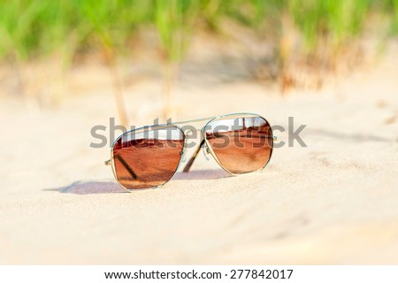 Trendy sunglasses with reflection lost on the beach sand. Multicolored outdoors closeup image. - stock photo