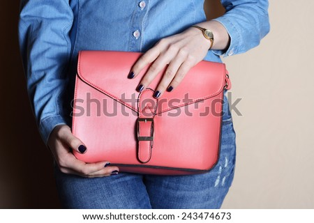 trendy woman in jeans and denim shirt with pink bag in hands beige background - stock photo