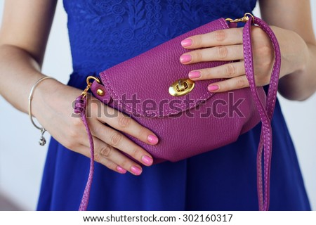 Trendy young girl holding  leather  purple little handbag . Summer spring accessory - stock photo