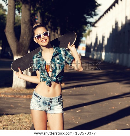Trendy young girl in summer dress with skateboard. Outdoors. Urban lifestyle shot. - stock photo