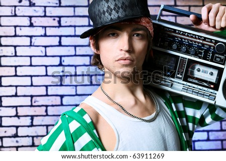 Trendy young man posing  against a brick wall with tape recorder. - stock photo
