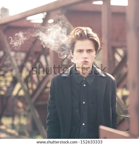 Trendy young man smoking outdoors - stock photo
