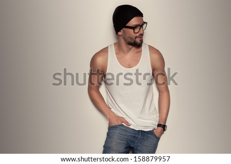 Trendy young man wearing blue jeans, a tank top and a beanie hat leaning against a wall - stock photo