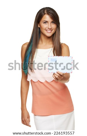 Trendy young smiling woman giving you blank envelope, over white background. Shallow depth of field, focus on envelope - stock photo