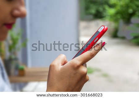 Trendy young woman use a smart phone in coffee shop blur - stock photo