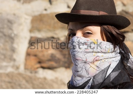 Trendy young woman wearing a scarf over her face like a bandit and a stylish hat looking sideways at the camera against a stone wall with copyspace - stock photo