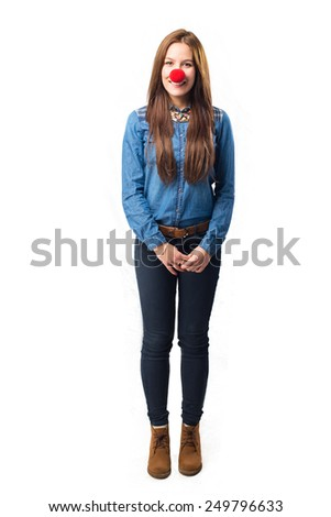 Trendy young woman with a red clown nose. Over white background - stock photo