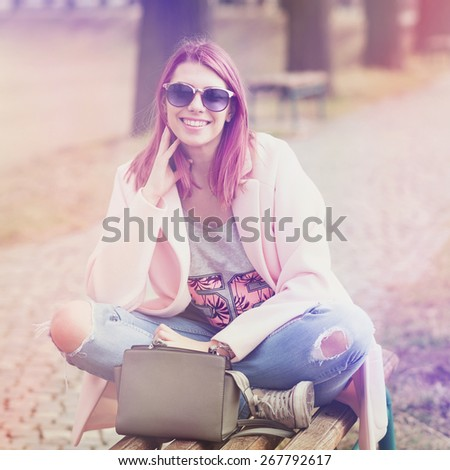 Trendy young woman with pink hair wearing fashionable denim jeans, pink coat and sunglasses smiling sitting on bench in park. Closeup, square format, retouched, color filter applied. - stock photo