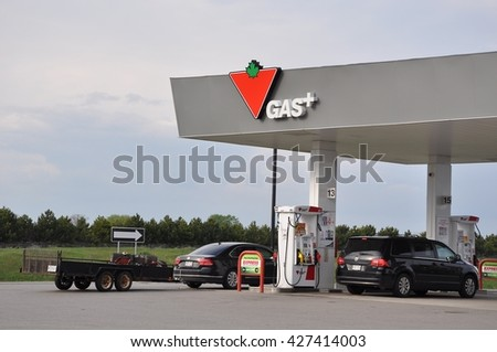 Trenton, Ontario, Canada - May 22, 2016: Drivers fill gas in Canadian Tire Gas station.  - stock photo