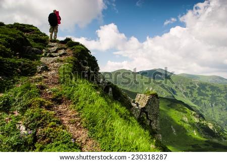 Treveler is hiking into the peak in Carpathian mountians - stock photo