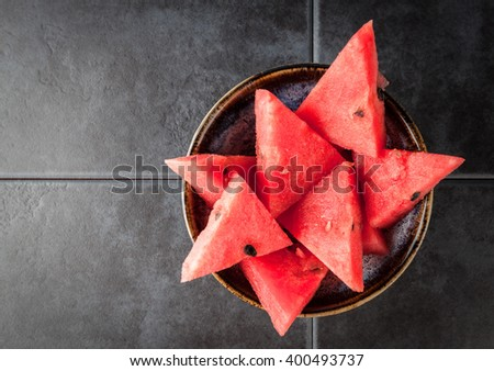 Triangle shaped watermelon slices placed in ceramic bowl on dark grungy background with copy space.  Top view. Shallow depth of field. - stock photo
