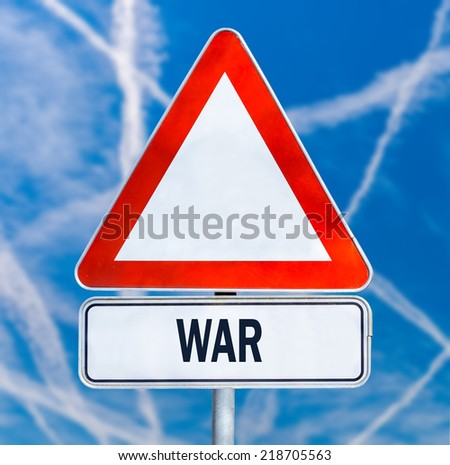 Triangular traffic warning sign with the word - War - against a blue sky criss-crossed by multiple white contrails from aircraft conceptual of a fight between enemy planes or anti aircraft missiles. - stock photo