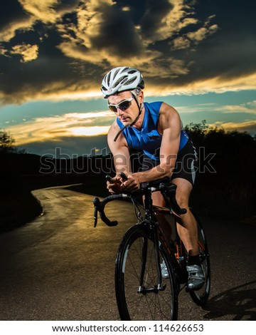 triathlete cycling in sunrise - stock photo