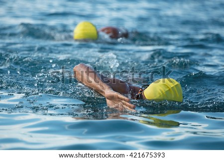 Triathlon swimmers churning up the water two swimmers in races in triathlon, with a front view - stock photo