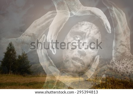 Tribal mask of a woman with sad eyes, glance, surrounded with gloving hands holding her on a landscape background .The image is about meditation, loneliness in the universe in search of spirituality - stock photo