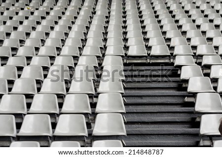 Tribune sports stadium, gray chairs arranged in rows - stock photo