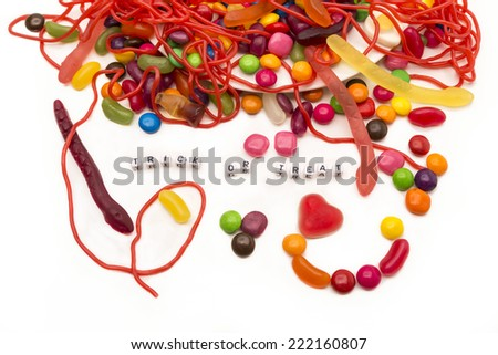 Trick or treat words surrounded by coloful candy beans, strings and worms from an overflowing dish onto a white background. Could work great as an kids party invitation. - stock photo