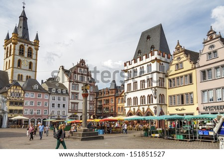 TRIER, GERMANY- AUGUST 9: Market square. This cental square came into existence in 10th century and marked by replica of original stone cross dates by 958 year, in Trier, Germany, on August  9, 2013  - stock photo