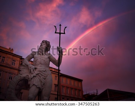 Trieste, Italy. A beautiful statue representing Neptune, aka Triton and Poseidon, and his classical trident with a stunning rainbow on the background. - stock photo