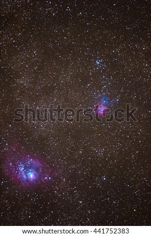 Trifid Nebula and Lagoon Nebula with an amateur DSLR Camera. - stock photo