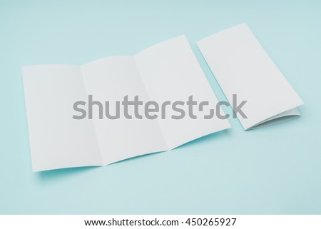 Trifold white template paper on blue background - stock photo