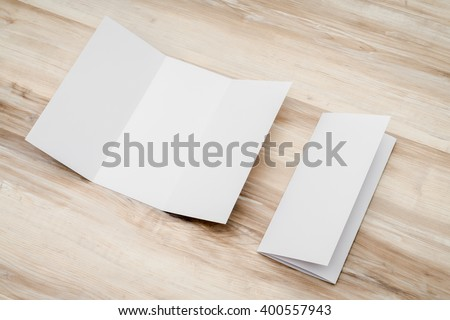 Trifold white template paper on wood texture - stock photo