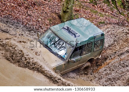 TRING, UK - NOVEMBER 25: An unnamed driver takes his Land Rover through a particularly muddy bombhole at the Burnham off Roaders winter trialling event on November 25, 2012 in Tring - stock photo