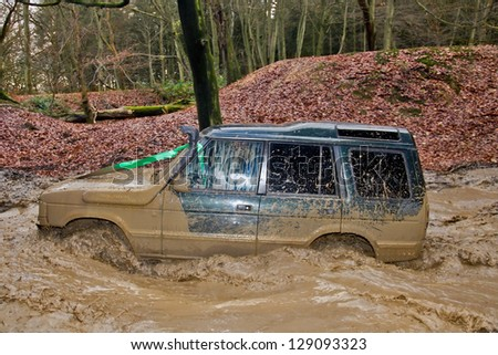 TRING, UK - NOVEMBER 25: Members of the Burnham Off Road club take a Land Rover Discovery through a water filled bombhole during the winter trialing competition event on November 25, 2012 in Tring - stock photo