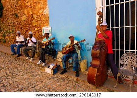 TRINIDAD, CUBA - DECEMBER 24, 2013: A group of unidentified musicians playing multiple instruments for the tourist in the cobble street in the historic part of Trinidad, Cuba on Christmas Eve 2013. - stock photo