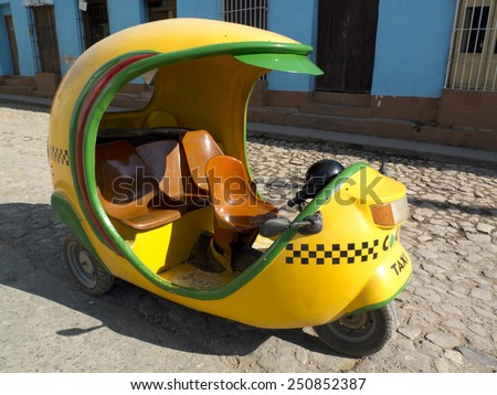 TRINIDAD, CUBA - DECEMBER 8: a yellow egg-shaped taxi is parked in a paved street , on december 8, 2014, in Trinidad, Cuba. - stock photo