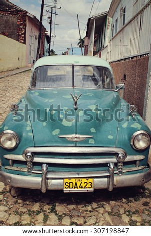 Trinidad, CUBA - FEB 28: Old classic American car park on street of Trinidad,CUBA on February 28 2007. Old American cars are iconic sight of Cuba street. - stock photo