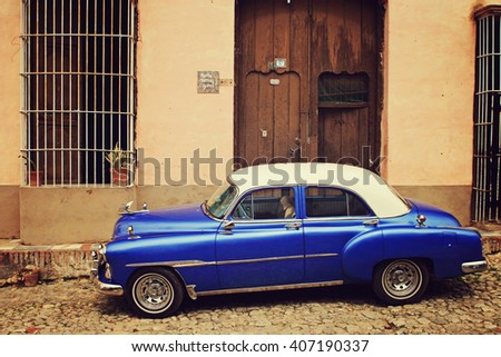 Trinidad, CUBA - FEB 28: Old classic American car park on street of Trinidad,CUBA on February 28 2007. Old American cars are iconic sight of Cuba street.  - stock photo
