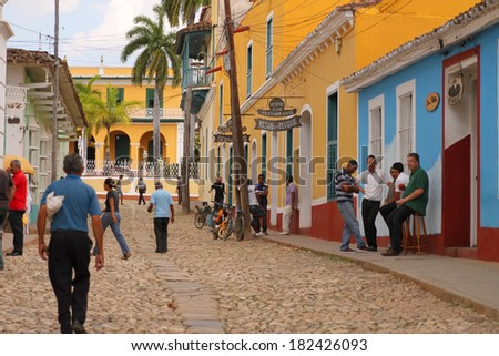 TRINIDAD, CUBA - FEBRUARY 25, 2014: Cuban people hanging out and crossing the cobblestone street in Trinidad, Cuba on February 25, 2014 - stock photo