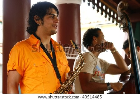 TRINIDAD, CUBA - MARCH 20, 2009: Salsa band performing on March 20, 2009 in Trinidad, Cuba. Employment options in Cuba are very slim, street salsa bands are very common and mostly entertain tourists. - stock photo