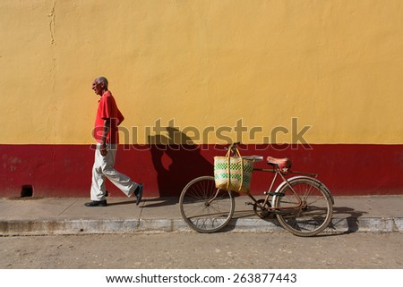 TRINIDAD - FEBRUARY 23: Streets of Trinidad with unknown man walking on February 23, 2015 in Trinidad. Old American cars are iconic sight of Cuba street. - stock photo