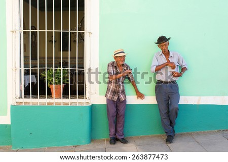 TRINIDAD - FEBRUARY 24: Unknown people smoking cigar on street of Trinidad on February 24, 2015 in Trinidad. Old American cars are iconic sight of Cuba street. - stock photo