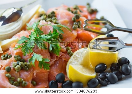 Trinley sliced salmon on plate with garnish - stock photo
