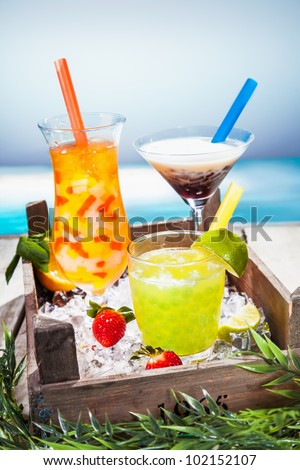 Trio of colourful tropical cocktails blended with fruit in different shaped glasses served overlooking a tropical beach - stock photo
