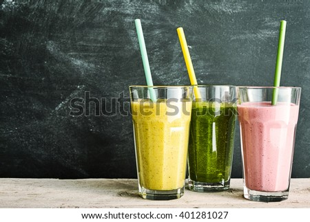 Trio of healthy fruit and vegetable smoothies - berry, kale and banana and almond - with straws on a rustic wooden table with slate background with copy space - stock photo