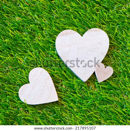 Trio of hearts in different sizes on green grass symbolic of love and romance for a Valentines Day, special occasion anniversary - stock photo
