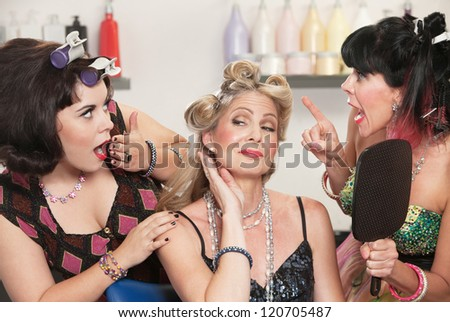 Trio of pretty Caucasian women showing off in hair salon - stock photo