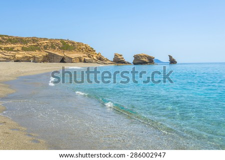 "Triopetra beach, Crete. The beach of Triopetra (meaning ""Three stones"", after the three rocks in the sea) is a long and wide sandy beach in the south of the island of Crete. - stock photo"