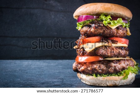 Triple American burger with cheese and grilled onions,selective focus and blank space  - stock photo