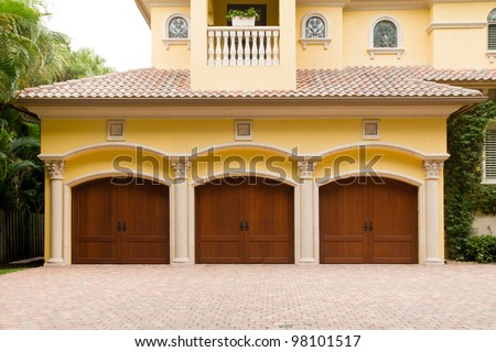 Triple garage with wooden doors - stock photo
