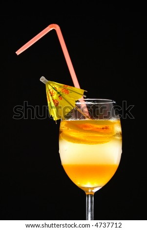 Triple layered drink with spiral lemon slice, umbrella and straw in studio light - stock photo